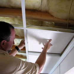 A contractor installing a suspended basement ceiling.